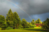 Rainbow above green trees and a log house — Stock Photo