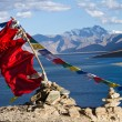 Stock Photo: Buddhist prayer flags on wind against blue lake, mountai