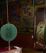 Prayer drum and wall paintings in the buddhist temple — Stock Photo