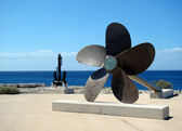 A big propeller and anchor located on the coast — Stock Photo