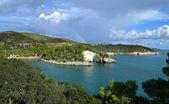 Rainbow over the rock window near Vieste — Stock Photo