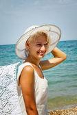 Chica con un sombrero en la playa. — Foto de Stock