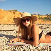 Girl on the beach wearing a straw hat — Stock Photo