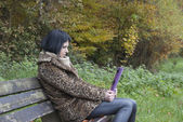 Alternative Model sat on a bench with a tablet PC — ストック写真