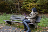 Alternative Model sat on a bench with a tablet PC — Stock fotografie