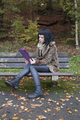 Alternative Model sat on a bench with a tablet PC — Foto Stock