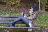 Alternative Model sat on Bench with Tablet PC — Стоковое фото