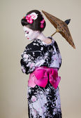 Japanese woman shows kimono with an umbrella — Stock Photo