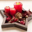 Star shaped dish with red candles and christmas decoration — Stock fotografie