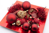 Red dish with christmas balls and christmas decoration isolated on white ba — Stock Photo