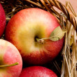Stock Photo: Fresh red apples in basket with straw at daylight