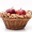 Red apples and nuts in a basket on white background — Stock Photo