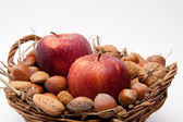 Red apples with waterdrops and nuts in a basket isolated on white background — Stock Photo