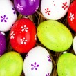 Colorful painted easter eggs hidden in a nest of straw — Stock Photo