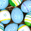 Colorful painted easter eggs hidden in a nest of straw - Stock Photo