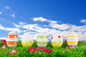 Coloridos huevos de pascua pintados situados en un prado con flores — Foto de Stock
