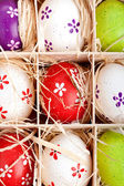 Assorted colorful painted easter eggs in a wooden box — Stock Photo