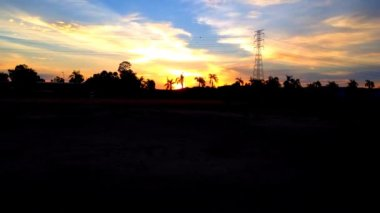 Pôr do sol timelaps perto de torres de cabo elétrico — Vídeo stock