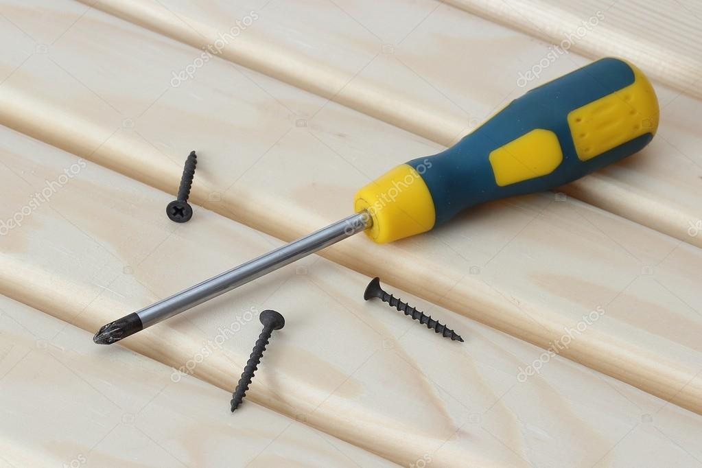 Screwdriver and three screws over wood  Stock Photo #14827421