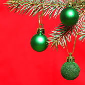 Branch of xmas tree with three green balls over red — Stock Photo