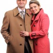 Happy couple dressed in coats on white background — Stock Photo