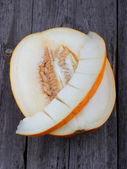 Sliced melon on old wood background — Stock Photo