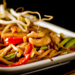 Stir-fried chinese noodles with chicken, vegetables and beansprouts on black — Stock Photo #13518664