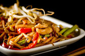 Stir-fried chinese noodles with chicken, vegetables and beansprouts on black — Photo