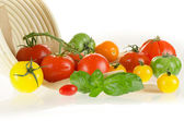 Different types of tomatoes of different colors with basket and — Stock Photo