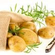 Fresh ripe potatoes and rosemary with burlap sack and knife — Stock Photo #13770269