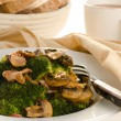 Broccoli sauteed with bacon and mushrooms served on a white plat — Stock Photo