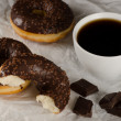 Chocolate donuts with coffee and chocolate pieces on crumbled ba — Stock Photo