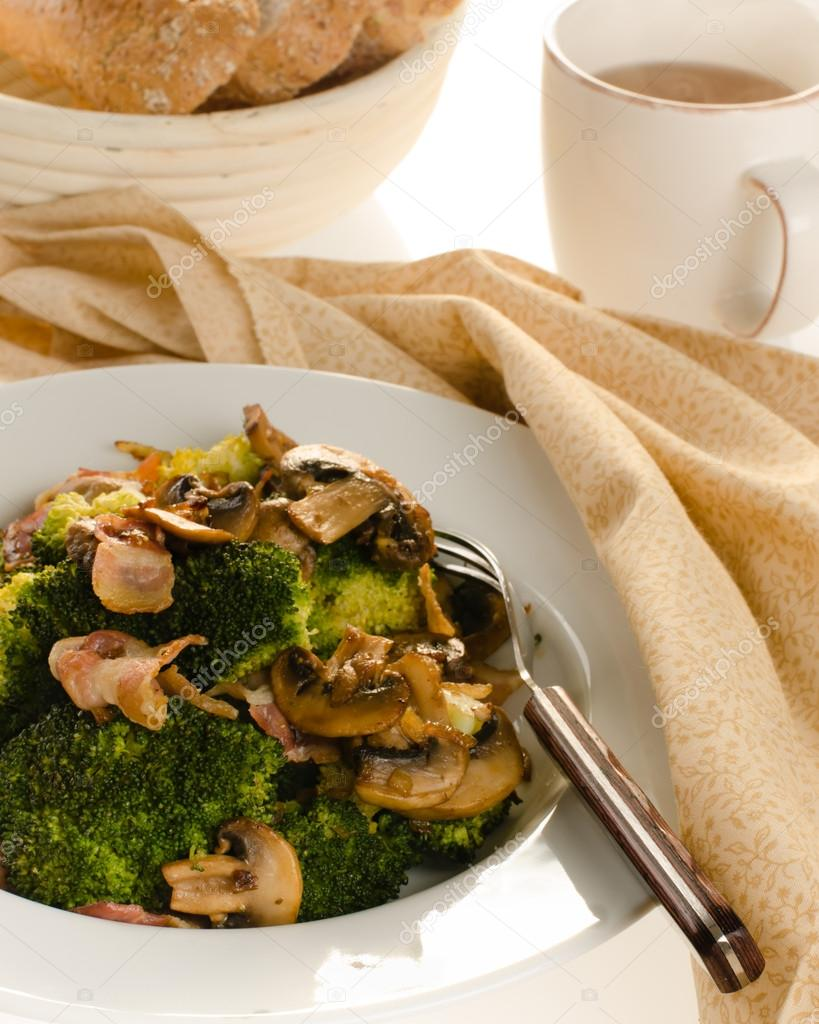 Broccoli sauteed with bacon and mushrooms served on a white plate with bread and tea isolated on white backgtround — Stock Photo #17200657