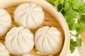 Chinese steamed buns in bamboo steamer basket with cilantro on w — Stock Photo