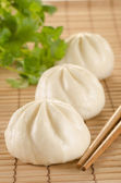Chinese steamed buns on the bamboo mat background with chopstick — Stock Photo