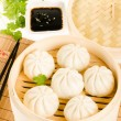 Chinese steamed buns in bamboo steamer basket with cilantro, soy — Stock Photo