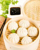 Chinese steamed buns in bamboo steamer basket with cilantro, soy — Стоковое фото