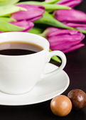 White cup of coffee with chocolate candies and purple tulips — Stock Photo