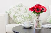 Vas med röda blommor i modernt vitt vardagsrum — Stockfoto