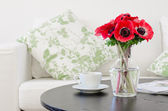 Vase των κόκκινα λουλούδια στο μοντέρνο λευκό σαλόνι — Φωτογραφία Αρχείου