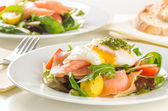 Poached egg salad with smoked salmon, cherry tomatoes and pesto. — Stock Photo
