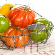 Fresh heirloom tomatoes in a basket isolated on white - Stock Photo