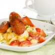 breakfast of scrambled eggs with tomatoes and chorizo sausage on — Stock Photo