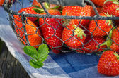Strawberries in the basket on wooden table — Stock Photo