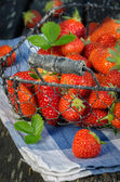 Strawberries in the basket on old garden wooden table — Stock Photo