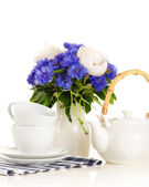 Tea pot and cups on table with blue and white bouquet on white b — Stock Photo