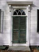 Vintage front door with shutters — Stock Photo