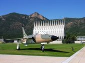 Military base church and an old retired fighter jet. — Stock Photo