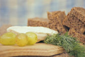 Appetizer ingredients: white cheese, dill, rye bread, grapes — Stock Photo