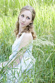 Photo of young blonde woman sitting in the green grass and looki — Stok fotoğraf